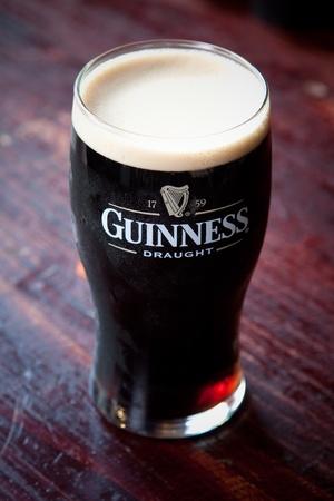 Koud, verfrissende pint Guinness stout Redactioneel