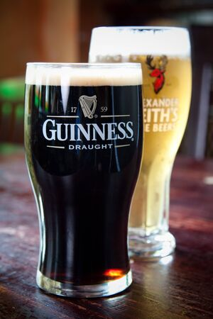 Chilled Pints of Guinness and Alexander Keiths in a pub setting.