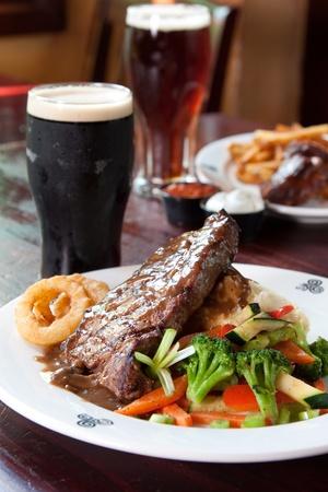 10 oz. New York Striploin Angus steak overgoten met Ierse whiskey jus, gebakken champignons en ui ringen. Geserveerd met verse groenten en aardappelpuree. Gaat het beste met Guinness. Focus op de voorkant van de biefstuk. Stockfoto