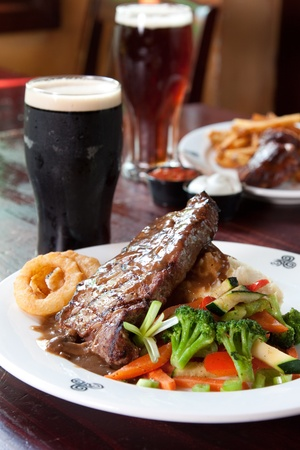 pub food: 10 oz. New York Striploin Angus steak topped with Irish whiskey gravy, sautéed mushrooms and onion rings. Served with fresh vegetables and mashed potatoes. Goes best with Guinness. Focus on the front of the steak. Stock Photo