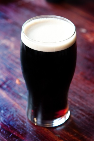 cerveza negra: Pinta de cerveza helada en un ambiente de pub.