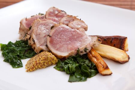 Sumptuous dinner of thinly sliced pork served with wilted spinach and roasted parsnips. Dijon mustard completes the flavors. Stock Photo - 11741892