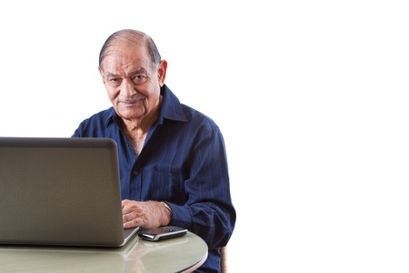 asian laptop: Portrait of a smiling elderly East Indian businessman on his computer laptop