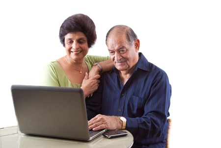 Portrait of a smiling elderly East Indian couple on computer laptop Stock Photo