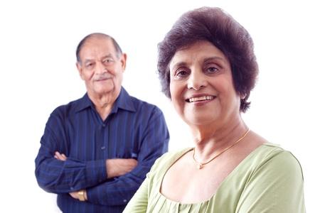 Portret van een lachende oudere Indische vrouw met haar man op de achtergrond