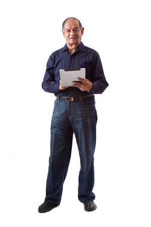 Portrait of a smiling elderly East Indian businessman using an iPad digital tablet photo