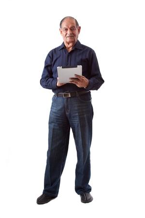 Portrait of a smiling elderly East Indian businessman using a digital tablet