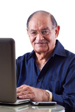 Portret van een lachende oudere Indische zakenman op zijn computer laptop Stockfoto