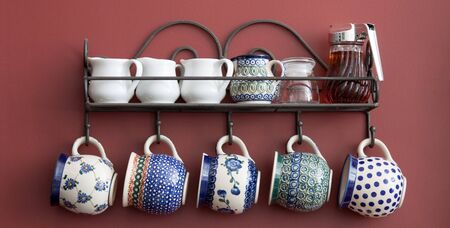 A beautiful arrangement of cups and saucers on a kitchen wall