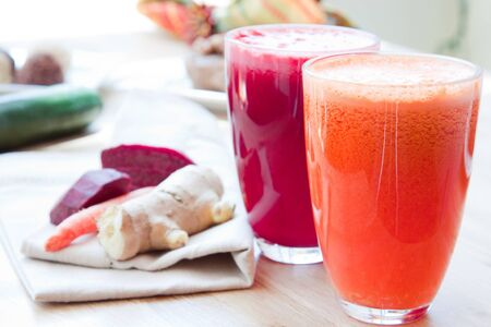 Two glasses of healthy juice - Beet, Apple, Carrot, Ginger and Orange, Apple, Pineapple  Ingredients in the background