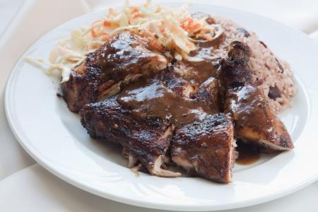 vergezeld: Caribische stijl geroosterde kip geserveerd met rijst gemengd met rood bruine bonen schotel vergezeld met koolsla Ondiepe Focus op de kip Stockfoto