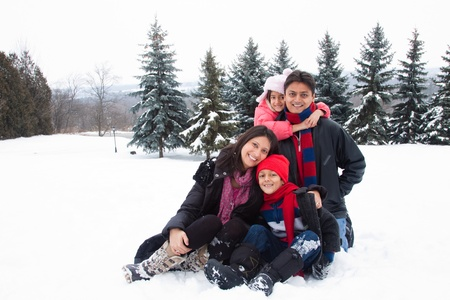 A beautiful East Indian parents play with her children in the snow. photo