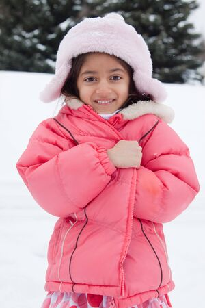 clutches: A beautiful East Indian girl child clutches to her jacket in the snow.