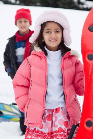 A brother and a sister get ready to go toboganning in the snow. photo