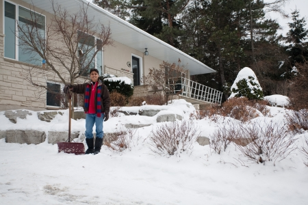 A young East Indian man shovels snow outside his house photo