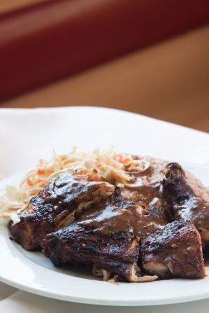 kidneybohnen: Karibischen Stil Jerk Chicken serviert mit Reis mit roten Bohnen gemischt. Dish mit Krautsalat. Shallow Focus on the chicken.