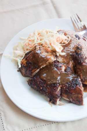 jamaican food: Caribbean style jerk chicken served with rice mixed with red kidney beans. Dish accompanied with coleslaw. Shallow Focus on the chicken.
