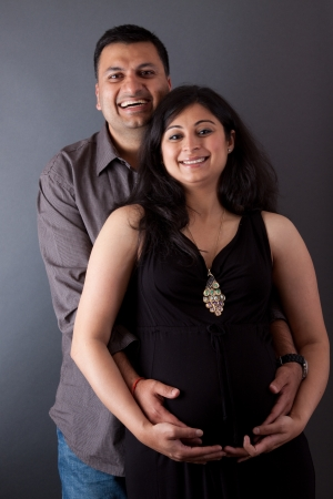 An East Indian couple holding the belly of the pregnant wife photo
