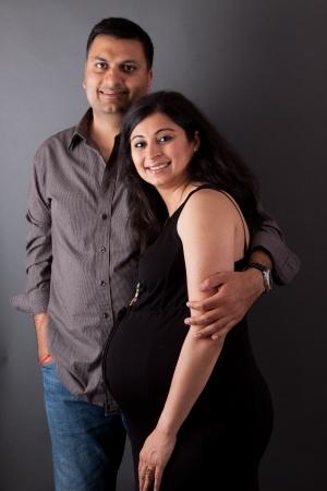 esposas: Un hombre de East Indian abraza a su esposa embarazada