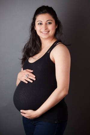 Portrait of a smiling, pregnant East Indian woman holding her belly