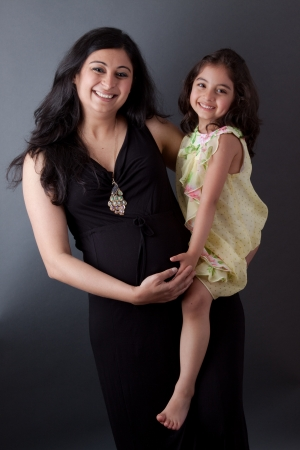 Portrait of a smiling, pregnant East Indian woman sitting with her daughter. The woman is wearing a formal gown.