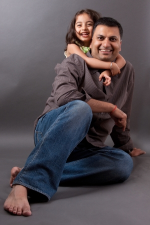 Portrait of an East Indian man laughing with his daughter