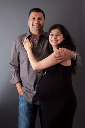An East Indian man embraces his pregnant wife photo