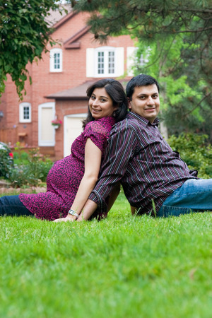 Image of an East Indian man sitting outside with his pregnant wife photo
