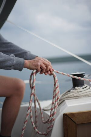 Close up of hands coiling up a rope, sheet on a sailboat