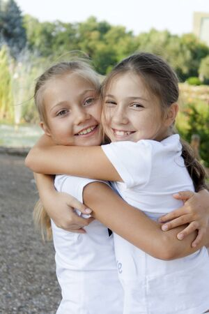 little girl embraces the sister in park