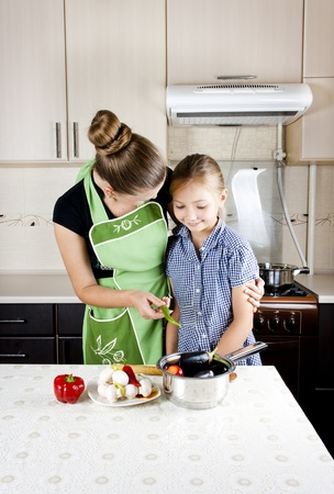 young woman with a daughter in the kitchen preparing photo