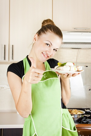 young woman cooks dinner in the kitchen