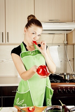 young woman cooks dinner in the kitchen photo