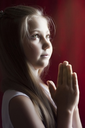 head in hands: little girl praying for their parents and peace