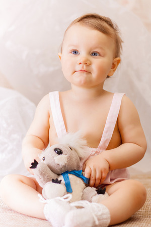 Little girl with a soft toy bear Stock Photo