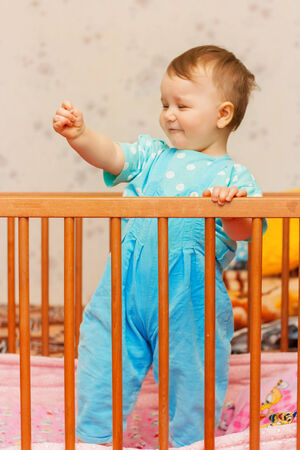 Funny little boy dancing in bed Stock Photo