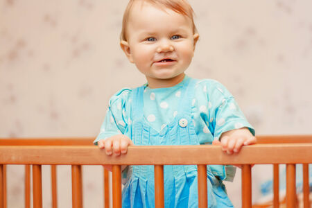 Funny little boy standing in the crib and smiling Stock Photo
