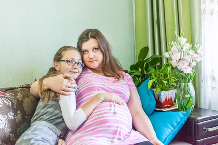 Pregnat woman resting at home with her little daughter Stock Photo