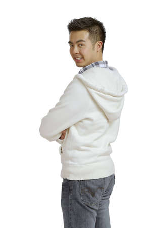 fold back: A three quarter view from the rear of a young Asian man standing with his face turned toward the camera
