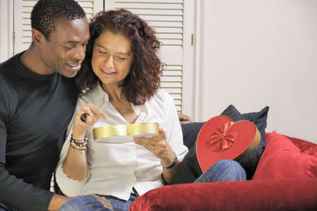 mixed-race couple looking into a chocolate box together