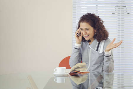 Smiling happy woman with coffee and a book, sitting at a table and talking on the phone. Stock Photo