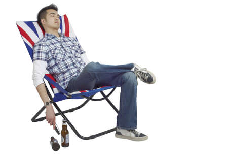 folding chair: Young Asian man asleep in a chair with a remote in his hand and beers on the floor.