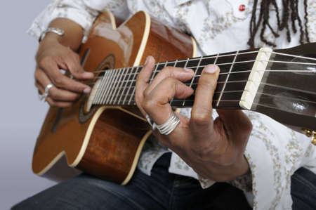 close up of a mans fingers holding a chord on the acoustic guitar Stock Photo