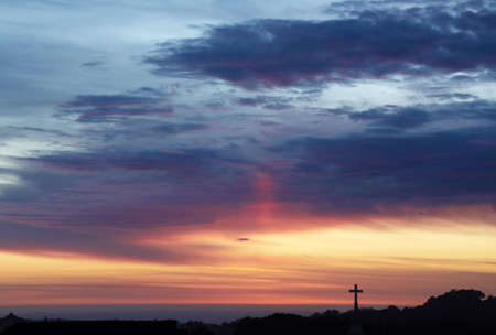 Sunset sky with the silhouette of a cross breaking the horizon
