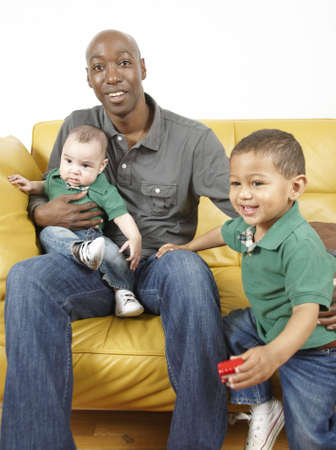 A father sitting on a couch tending to his 2 mixed race boys Stock Photo