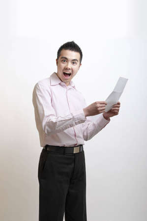 Young Asian man excited by the letter he has just read photo