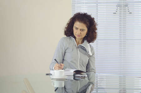 Woman sitting at a glass table writing in her journal
