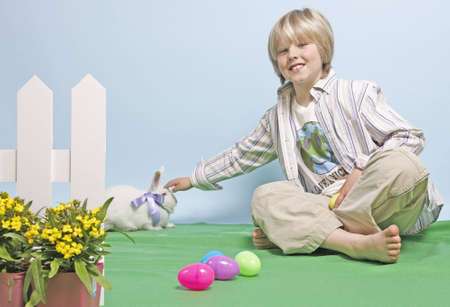 Blonde seated boy reaches out to pet a white rabbit wearing a bow Stock Photo