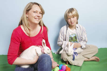 Mother and son put ribbons on their pet rabbits in preparation for Easter