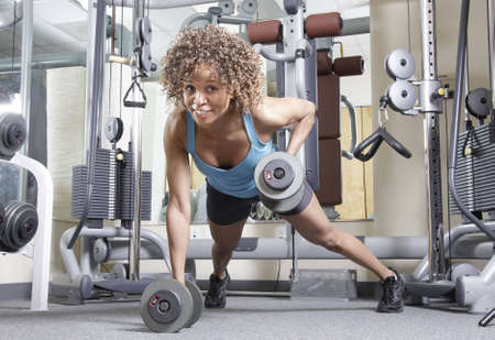 Woman working out with weights in a gym Stock Photo